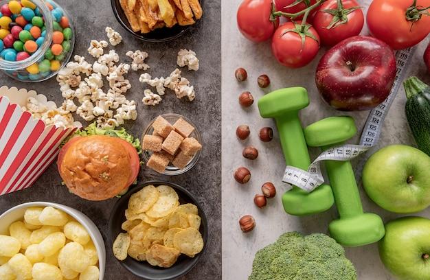 Fruits et légumes vs bonbons et pommes de terre frites vue de dessus à plat