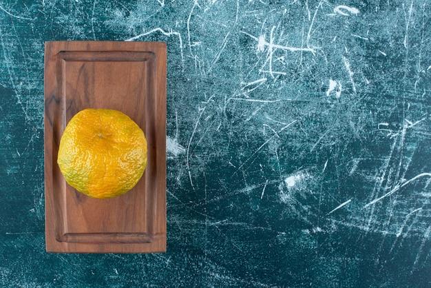 Fruits de mandarine frais sur planche de bois.