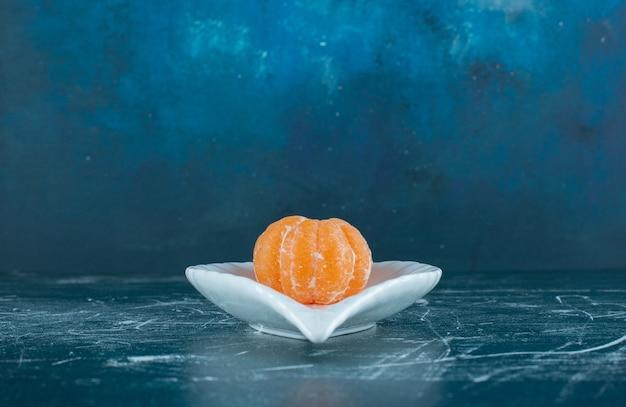 Fruits de mandarine pelés sur plaque blanche.