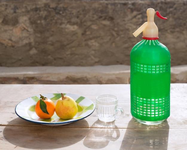 Fruits mandarine et poire dans une bouteille de soda plat vintage