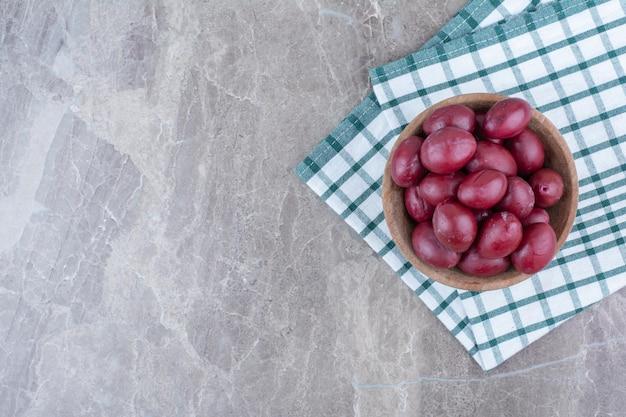Fruits marinés dans un bol en bois avec nappe.
