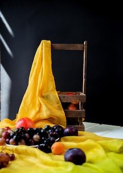 Fruits mélangés sur un ruban jaune sur une table blanche et un panier de fruits autour.