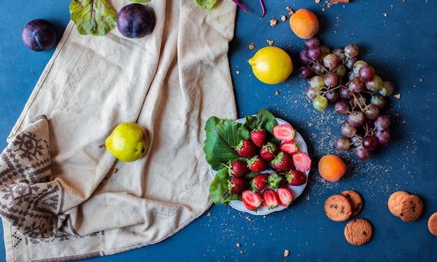 Fruits mélangés sur une table bleue.