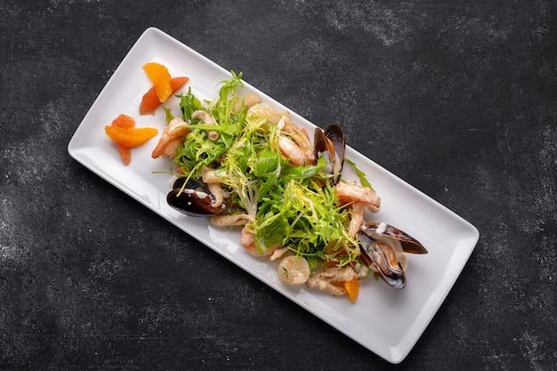Fruits de mer sur une assiette, moules, pétoncle, crevettes, calamars, avec mélange de salade sur fond sombre
