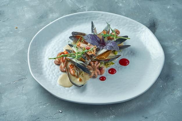 Fruits De Mer Cuits Dans Une Sauce Crémeuse. Moules, Poulpe Et Crevettes Avec Sauce Dans Une Assiette Blanche Photo Premium