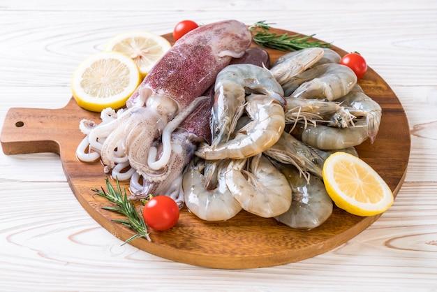 Fruits de mer frais crus (crevettes, calamars) sur une planche de bois