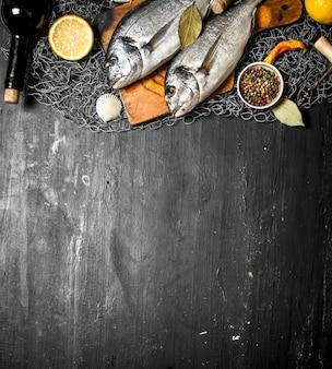 Fruits de mer frais. différents fruits de mer aux épices sur filet de pêche sur tableau noir.