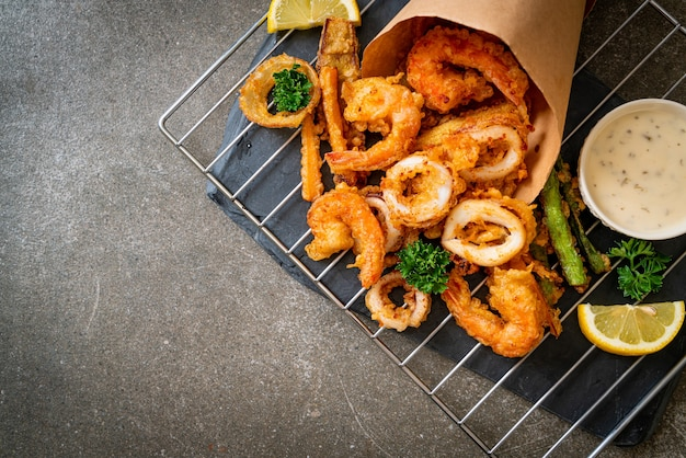 Fruits de mer frits (crevettes et calmars) avec mélange de légumes - style de nourriture malsaine