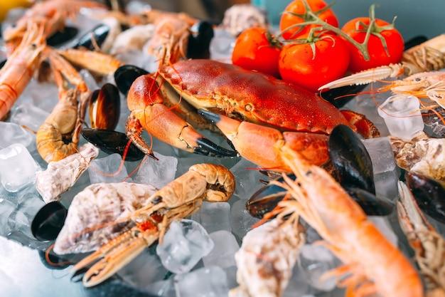 Fruits de mer sur glace. crabes, esturgeons, crustacés, crevettes, rapana, dorado, sur glace blanche.