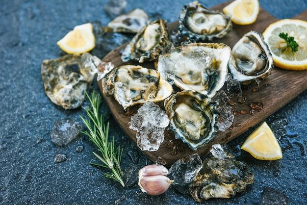 Fruits de mer d'huîtres fraîches sur une planche en bois. coquille d'huître ouverte avec des épices aux herbes, romarin au citron, table servie et glace fruits de mer sains dîner d'huîtres crues au restaurant