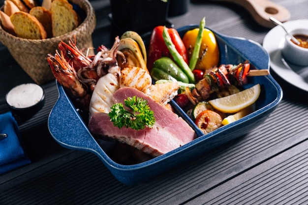 Fruits de mer mélangés grillés tels que poissons, calmars, crevettes roses, moules et légumes.