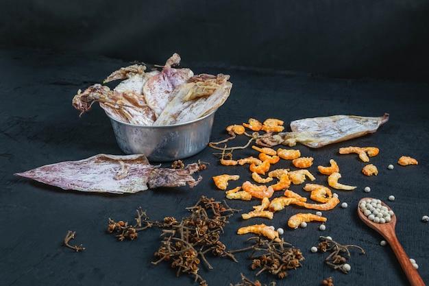 Fruits de mer séchés avec calamars séchés et crevettes séchées sur une table en bois noire