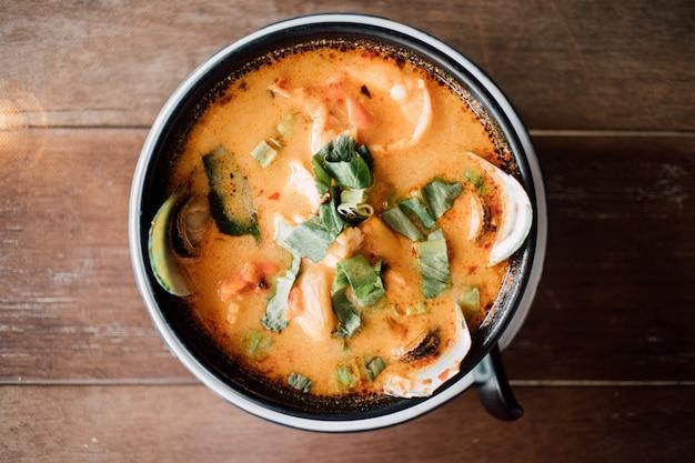 Fruits de mer thaï crémeux tom yum servis dans un bol.