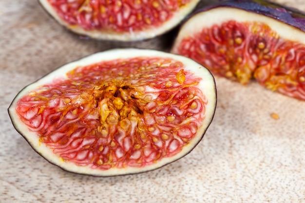 Fruits mûrs dans la cuisine lors de la préparation de la salade de fruits rouge délicieux pulpe de figue avec des graines de figues mûres coupées en morceaux