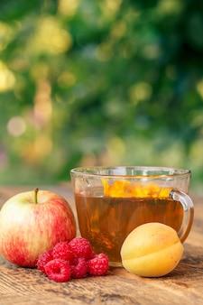 Fruits mûrs de pomme, abricot et framboises et tasse de thé vert aux fleurs de calendula.