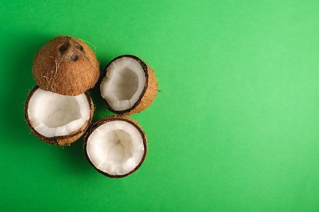 Fruits de noix de coco sur mur uni vert, concept tropical de nourriture abstraite, vue de dessus copie espace
