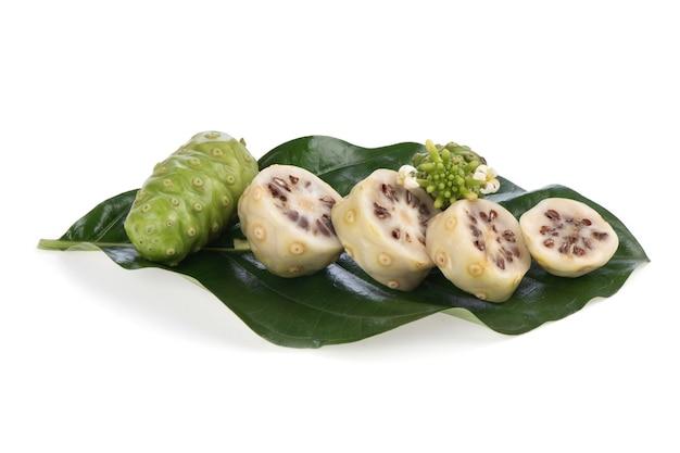 Fruits de noni sur feuilles vertes et isolés sur fond blanc.
