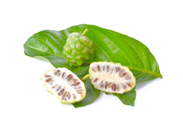 Fruits de noni sur grande feuille verte sur une surface blanche