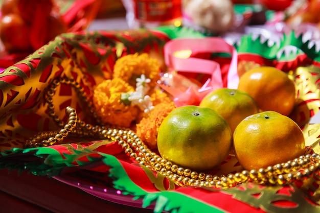 Fruits orange, chapelet, fleur et drapeau de prière dans un temple bouddhiste chinois