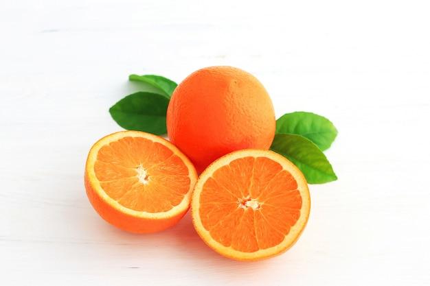 Fruits orange et un coupé en deux, avec des feuilles isolées sur fond blanc.