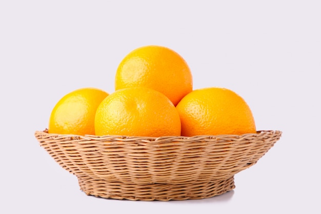 Fruits orange dans le panier sur un fond blanc