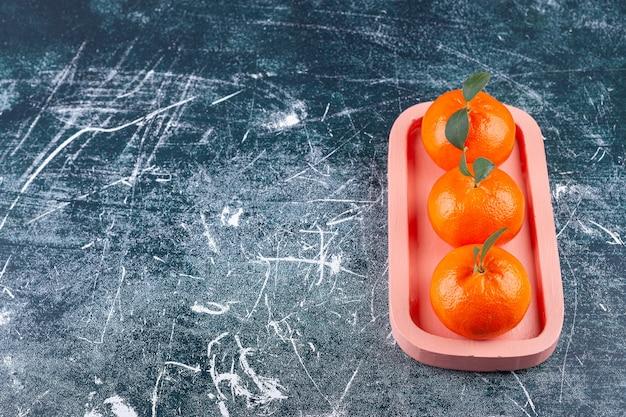 Fruits orange entiers avec des feuilles vertes placées sur une assiette blanche.