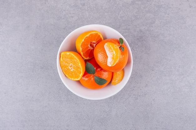 Fruits orange entiers avec des feuilles vertes placées sur la surface de la pierre.