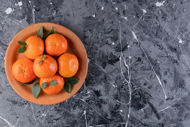Fruits orange frais entiers avec des feuilles placées dans une assiette en argile.
