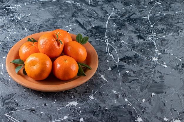 Fruits orange frais entiers avec des feuilles placées dans une assiette d'argile