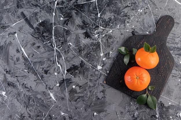 Fruits orange frais entiers avec des feuilles placées sur un tableau noir.