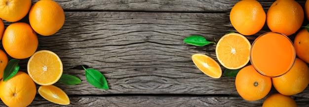 Fruits orange frais avec des feuilles sur une table en bois verre de jus d'orange frais
