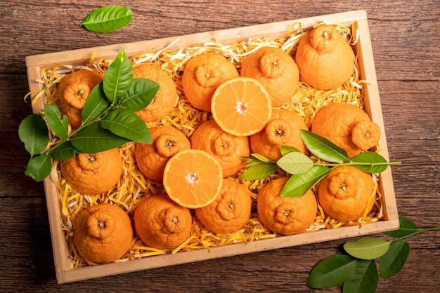 Fruits orange avec des tranches d'orange et des feuilles dans une boîte en bois, dekopon orange ou mandarine sumo avec des feuilles dans une boîte d'emballage.