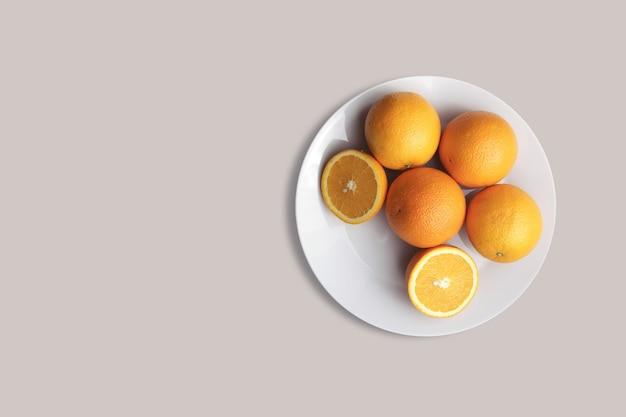 Fruits oranges frais sur une plaque blanche pour le menu. fond géométrique. mise à plat, espace de copie, vue de dessus.