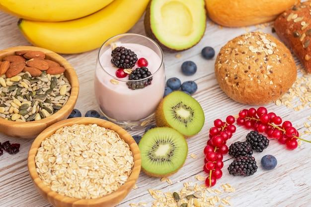 Fruits et pain grains entiers et noix sur table en bois