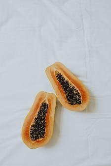 Fruits de papaye orange exotique tropical allongé sur le lit avec des draps blancs