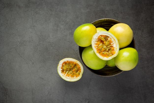 Fruits de la passion frais coupés en deux mis dans un bol noir