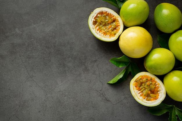Fruits de la passion frais coupés en deux sur un sol sombre