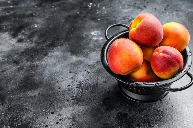 Fruits de pêches dans une passoire noire sur la table.