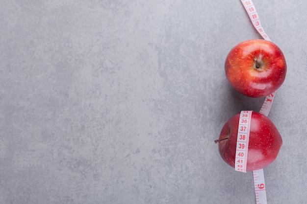 Fruits de pomme mûrs rouges placés sur une table en pierre.