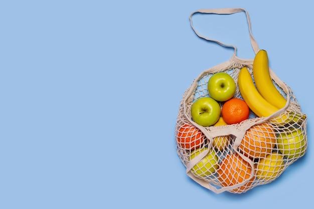 Fruits pommes dans un sac à provisions écologique sur fond bleu
