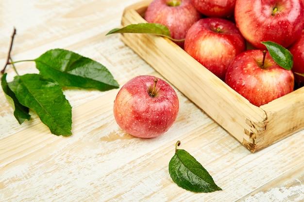 Fruits de pommes mûres rouges fraîches dans la boîte en bois.