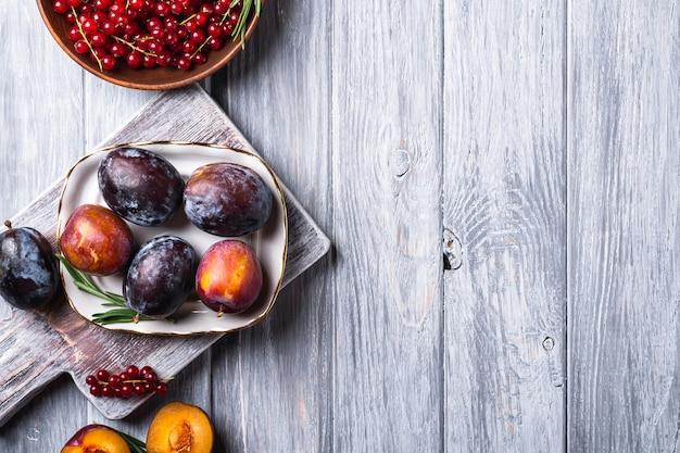 Fruits de prune doux frais entiers et tranchés dans une assiette avec des feuilles de romarin sur une vieille planche à découper avec des baies de groseille rouge dans un bol en bois, fond de bois gris, vue de dessus copie espace