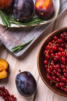 Fruits de prune doux frais entiers et tranchés dans une assiette avec des feuilles de romarin sur une vieille planche à découper avec des baies de groseille rouge dans un bol en bois, fond de table en bois, vue d'angle