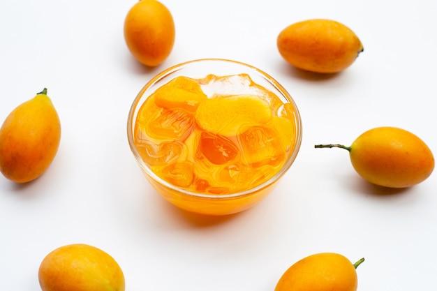 Fruits de prune mariale au sirop avec de la glace dans un bol en verre sur une surface blanche