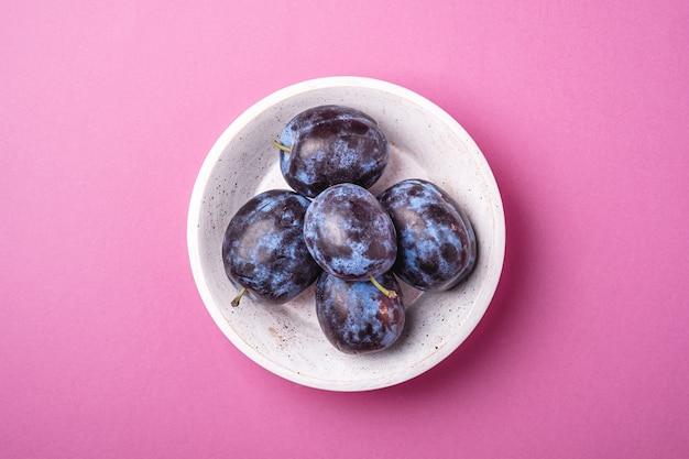 Fruits de prune mûrs frais dans un bol en bois blanc sur fond minimal rose, vue du dessus