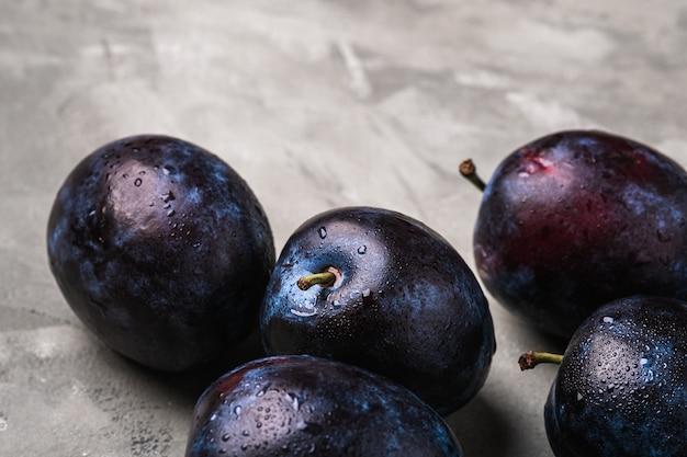 Fruits de prune mûrs frais avec des gouttes d'eau sur le béton de pierre, vue d'angle macro