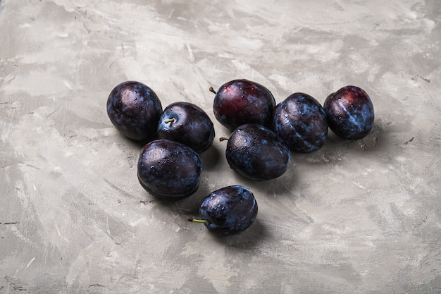 Fruits de prune mûrs frais avec des gouttes d'eau sur le béton de pierre, vue d'angle