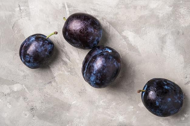 Fruits de prune mûrs frais avec des gouttes d'eau sur le béton de pierre, vue de dessus en gros plan