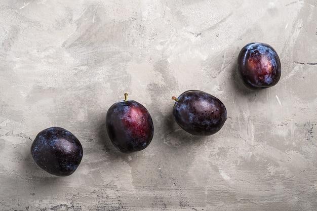 Fruits de prune mûrs frais avec des gouttes d'eau sur le béton de pierre