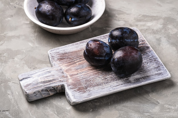 Fruits de prune mûrs frais avec des gouttes d'eau dans un bol en bois et une planche à découper